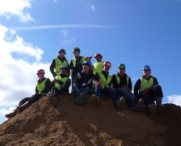 Group of young people wearing hard hats sitting on an earth mound. Photo taken at Build Camp