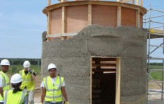 A student stands in front of a half-finished hempcrete tower