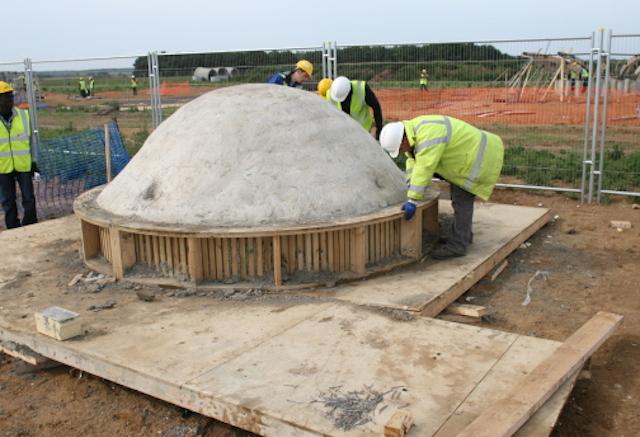 A site operative smoothes wet concrete in dome-shaped formwork