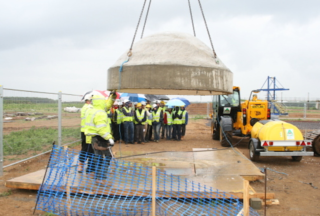 Foreground - a concrete dome is lifted by an excavator; background, twenty students look on under umbrellas