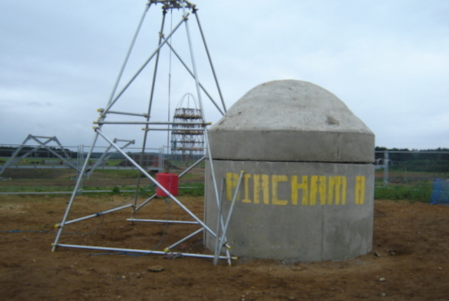 A scaffolding a-frame is erected adjacent to a concrete cylinder. A concrete weight hung on a pendulum is swung into the concrete structure to test its impact.