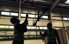 Two students use a block and tackle to lift a pipe over their heads.