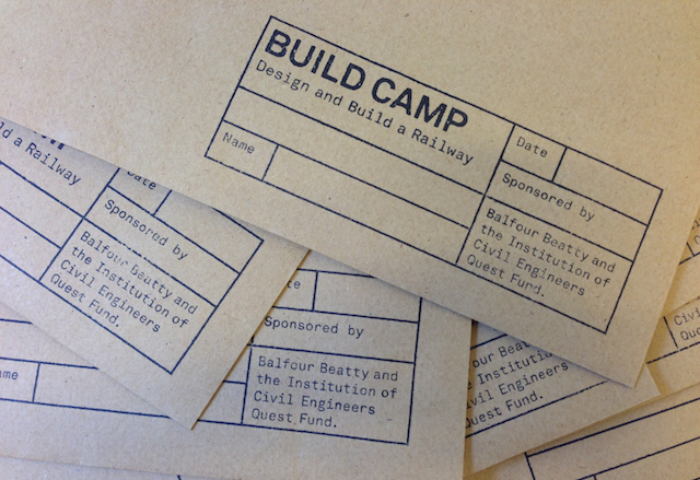 Images showing the Build Camp logo printed using a rubber stamp onto brown card