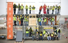 Image showing a three-storey scaffolding frame, called the Big Rig, on which forty people are smiling for a photograph.