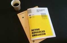 Image shows front cover of the Active Advanced Urbansim booklet and a cup of coffee
